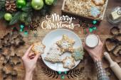 Fotografia ritagliata colpo delluomo che tiene il biscotto di Natale fatti in casa e vetro di latte su superficie di legno con la scritta Buon Natale