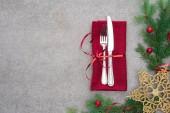 flache Liege mit Gabel und Messer umwickelt mit roter Schleife auf Tisch mit immergrünem Zweig verziert mit Weihnachtskugeln und goldenem Weihnachtsstern
