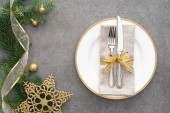 elevated view of plate with fork and knife wrapped by golden ribbon near evergreen branches decorated by christmas balls and golden star
