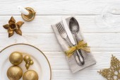 Photo view from above of plate with golden christmas balls, candle and fork, spoon, knife wrapped by ribbon on wooden table