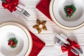 Photo elevated view of served table with candle, forks, knives and plates with evergreen branches decorated by christmas balls