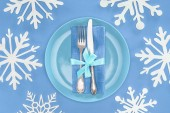 elevated view of fork and knife wrapped by festive ribbon on plate surrounded by snowflakes isolated on blue