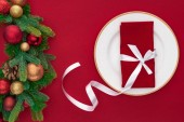 Fotografie top view of napkin wrapped by festive ribbon on plate near evergreen tree branches with christmas balls isolated on red