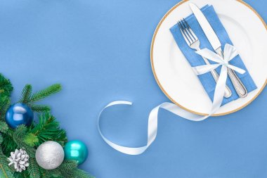 View from above of fork and knife wrapped by festive ribbon on plate near evergreen tree branches with christmas balls isolated on blue stock vector