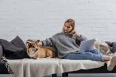 vážné mladá žena sedí s welsh corgi pembroke pes na pohovce a pomocí přenosného počítače