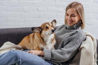 smiling young woman lying on sofa with adorable pembroke welsh corgi dog