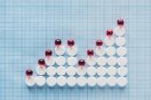 erhöhte Ansicht der Graphik von roten und weißen Pillen auf blau karierter Oberfläche