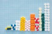 Ansicht der Graphik von verschiedenen bunten Pillen auf blau karierter Oberfläche
