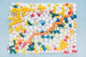 Fotografie top view of rectangle made of various colorful pills on blue checkered surface