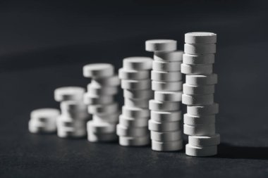 selective focus of stacks of white pills placed in rows on grey
