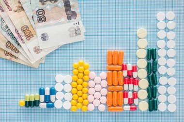 Top view of arranged stacks of white pills near russian rubles on blue checkered surface stock vector