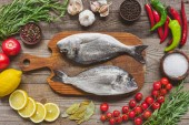 top view of raw fish on wooden board surrounded by ingredients on table