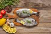 top view of raw fish on wooden board with rosemary and lemon on table