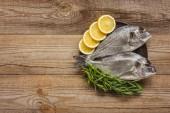 felső kilátás nyers hal, citrom és rozmaring fából készült asztal