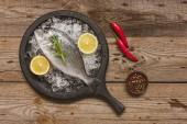 pohled shora na zásobník s tepelně neupravené ryb, rozmarýnem a citronovou na stole