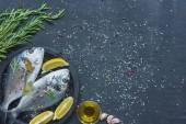 Nézd a fenti nyers hal, citromlé, babérlevél és a tálca fekete tábla hatálya só és bors rozmaring