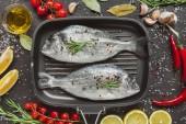 Blick von oben auf rohen Fisch im Backblech, umgeben von Zutaten auf schwarzem Tisch
