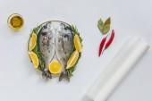 pohled shora pečícího papíru, olivový olej a ryby zdobená rozmarýnem a citronovou na desce