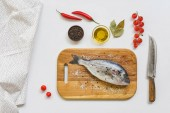Fotografie flat lay with uncooked fish on wooden board and various ingredients on white table