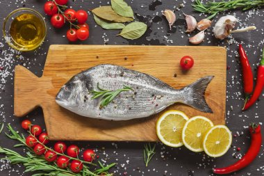 view from above of food composition with raw fish and ingredients on wooden board
