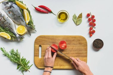 cropped image of woman cutting tomato by knife on wooden board near raw fish on table