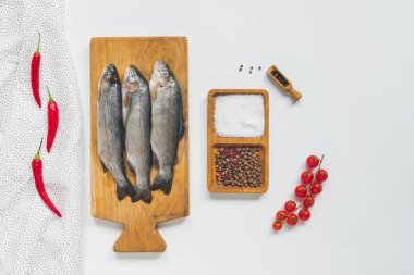 top view of uncooked fish on wooden board near ingredients on white table