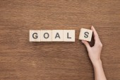 cropped view of person adjusting goals word made of wooden blocks on wooden tabletop, goal setting concept