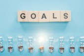 Draufsicht auf glühende Glühbirnen unter Ziele -Wort aus Holzklötzen auf blauem Hintergrund, Zielsetzungskonzept