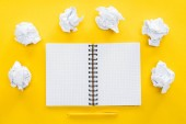 Photo blank spiral notebook and crumbled paper balls on yellow background