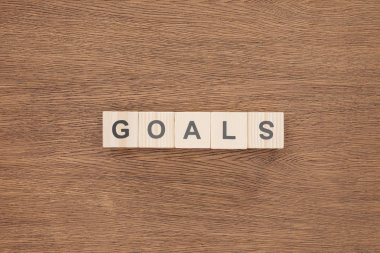 Top view of 'goals' word made of wooden blocks on wooden tabletop, goal setting concept stock vector
