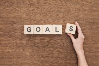 cropped view of person adjusting 'goals' word made of wooden blocks on wooden tabletop, goal setting concept