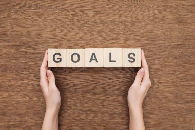 Partial view of person holding 'goals' word made of wooden blocks on wooden tabletop, goal setting concept stock vector