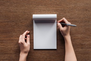 cropped view of person holding pen over blank notebook on wooden background
