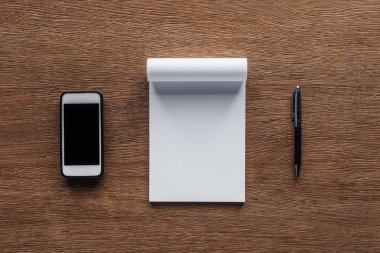 top view of pen, notebook with copy space and smartphone with blank screen on wooden background