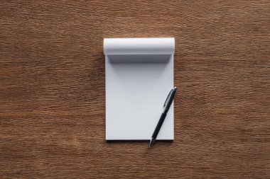 Blank notebook with pen on wooden background