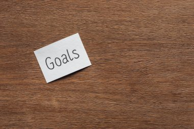 top view of 'goals' lettering on card with wooden background and copy space