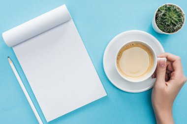 cropped view of person holding cup of coffee, blank notebook and pencil on blue background
