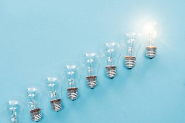 top view of light bulbs in row and one of them glowing on blue background, having new idea concept