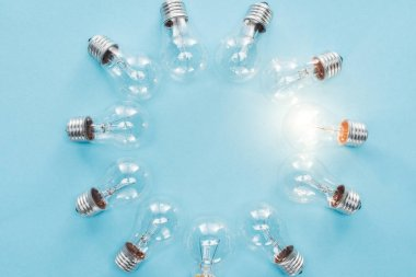 top view of light bulbs in circle and one of them glowing on blue background, having new idea concept