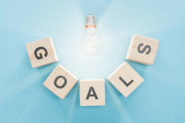 top view of glowing light bulb over 'goals' word made of wooden blocks on blue background, goal setting concept