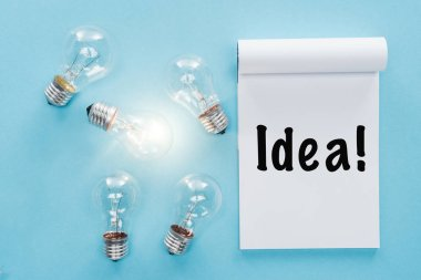 notebook with 'idea' word near light bulbs with glowing one, having new ideas concept
