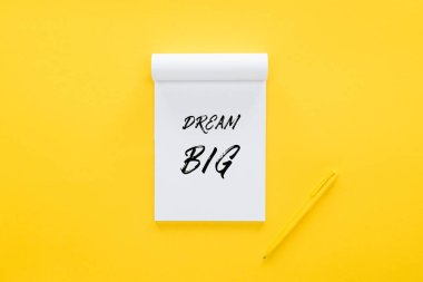 top view of notebook with 'dream big' quote on yellow, goal setting concept
