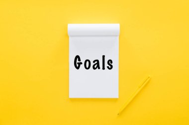 top view of notebook with 'goals' word on yellow, goal setting concept