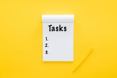 top view of notebook with tasks list on yellow