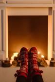 oříznutý pohled ženy v zimní vlněné ponožky s krbem na pozadí
