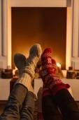 oříznutý pohled na ženy nosit zimní ponožky s krbem na pozadí