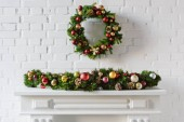 Photo festive christmas wreath over fireplace mantel with white brick wall