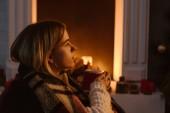 boční pohled na mladé ženy v kostkované dece hospodářství hrnek kakaa doma