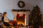 Photo  young woman on wicker rocking chair using laptop in living room decorated for christmas