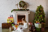 Photo  young woman sitting and using laptop in living room decorated for christmas